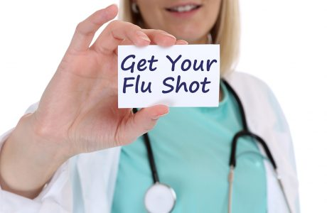 "clinician holding note saying ""get your flu shot"""