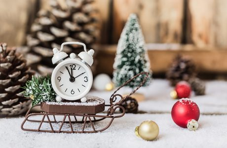 a tiny Christmas and New year scene with clock, snow on wooden sled and toys, and snowflakes texture